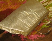 Pretty little gold fabric bag with architecturally interesting goldtone handle