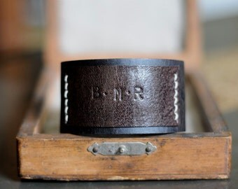 Personalised cow hide cuff with text of your choice stamped onto a kangaroo leather feature plaque