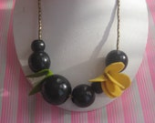 large black beaded necklace with yellow felt flower