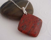 Red gemstone necklace -Tanger. Sterling silver necklace with wire wrapped brick red pendant.