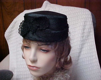 Black linen pill box hat with front decoration