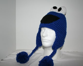 Crochet character hat with ear flaps and hanging pom poms inspired by Cookie Monster - fun and cute