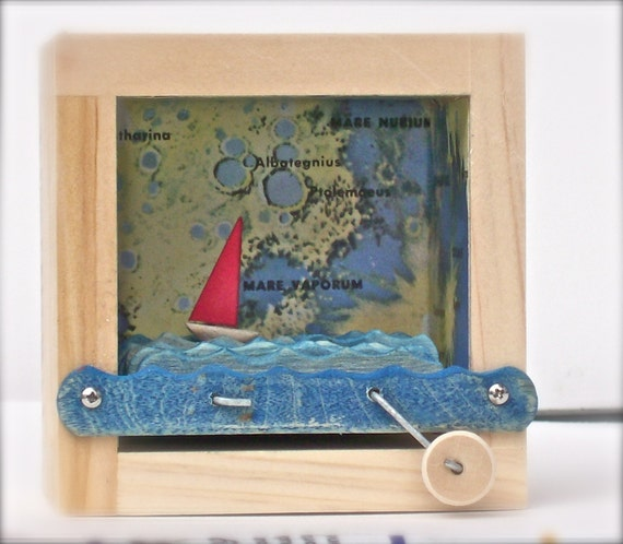 red sailboat in lunar map illustration box automaton