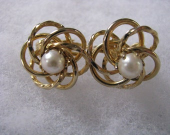Gold tone open swirl vintage clip on earrings with faux pearl center.
