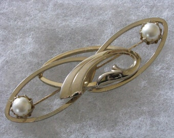 Oval gold tone metal pin brooch  intertwined with faux pearl
