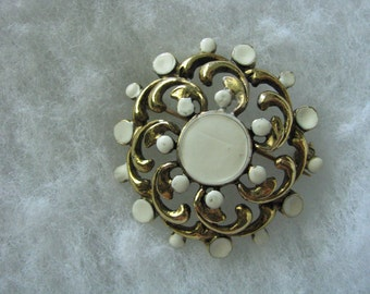 Gold tone swirly brooch pin creamy off white accents.