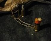 orange aventurine and feldspar growing from a spent .40 SW bullet casing