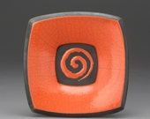 small orange\/poppy raku fired plate with spiral