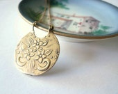 Gold necklace flower pendant. Detailed brass disk suspended from a delicate 14K gold fill chain.