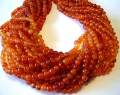 """Carnelian shaded round beads full 14"""" stand."""