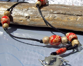 Beige, cream and red  flower patterned wood bead necklace on black cord with dolphin pendant, long necklace.