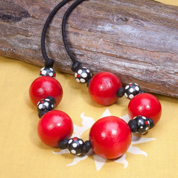 Red wood bead necklace, black red and white spotted beads on cord.