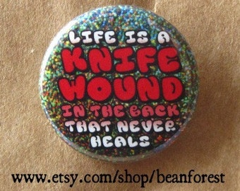 life is a knife wound in the back that never heals - pinback button badge