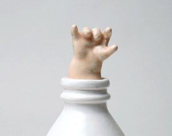 Baby Hand Emerging from Milk Bottle - Stopper with a Cause