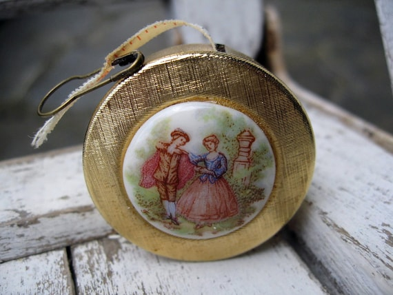 Vintage measuring tape with gold enamel inset, romantic figures