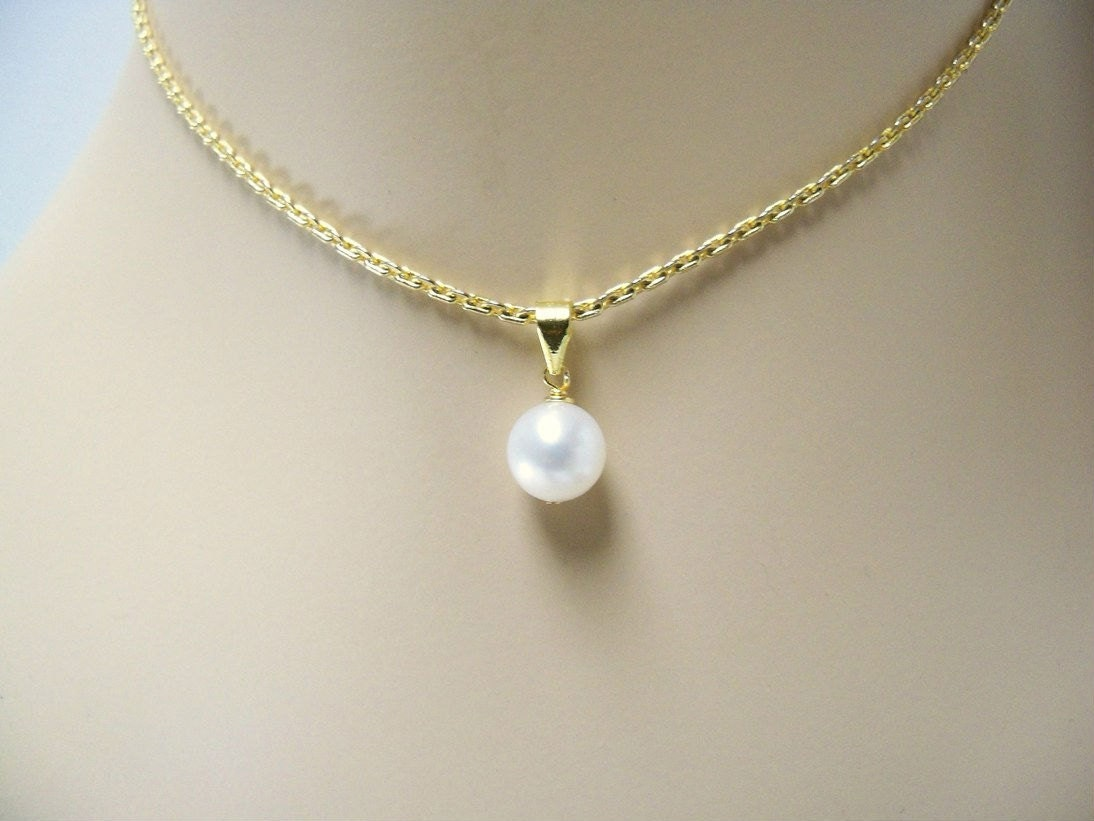 Single pearl pendant necklace wire wrapped on a gold plated