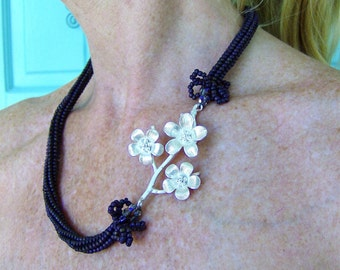 Swarvoski crystals in deep plum hues sparkle dramatically, transitioning the sleek glass beaded herringbone cord to the SS plum blossoms
