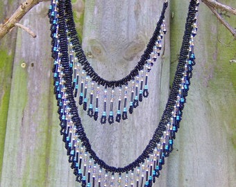 Thousands of beads in turquoise, white, periwinkle, amber and black cascade playfully from the black ribbon of beads as you move and walk