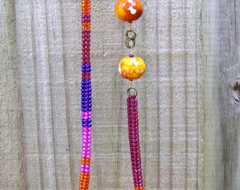 The Personality and Drama is in the agate stones in hot orange hues surrounded by brilliant orange, pink, purple & raspberry old world beads
