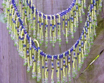 Over 7000 tiny glass beads are hand woven together creating the fringe and periwinkle herringbone ribbon of beads in this playful necklace