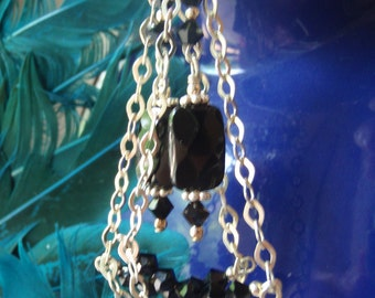 Sterling silver chain dangles with black onyx and crystal