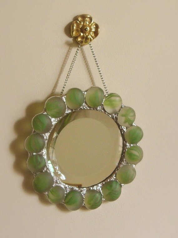 round mirror trimmed with frosted green nuggets