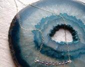 purple swarovski curve necklace.