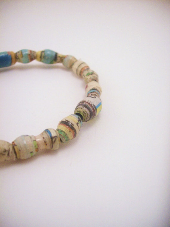 Stretchy newspaper beaded bracelet. Comics, news. Multicolored, blue, black, yellow,brown, peach. Paper. One size fits most.