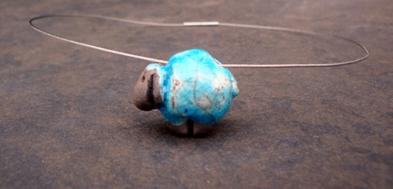 Ceramic sculpture of a sheep in turquoise on a wire necklace