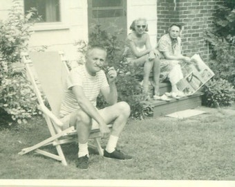 Vintage 1950s Summer Photo Man Smoking Pipe In Yard Women on Porch House Dress Reading Newspaper Bad Fashion Photograph