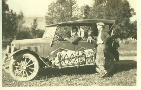 Traveling Man 1920s Photo Driving Sitting in Car With Puppy Dog Luggage Lashed to Side Board Summer Day Photograph Antique
