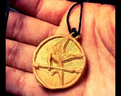 Hunger Games inspired gold mockingjay necklace on hemp string