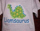 Dinosaur applique and Name Plus Saurus monogrammed on a T Shirt Sizes Newborn 3m 6m 9m 12m 18m 24m 2T 3T 4T 5T 6X 7 8 AND 10-12