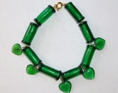 green glass bead bracelet with 5 hanging green hearts measures 7 1/2 inches long