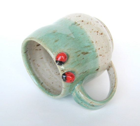 Green and speckled oatmeal mug with two ladybugs