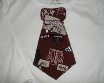 Size 0-3,3-6,6-9 or 12 months Months Long sleeved Aggie Onesie With Tie Applique