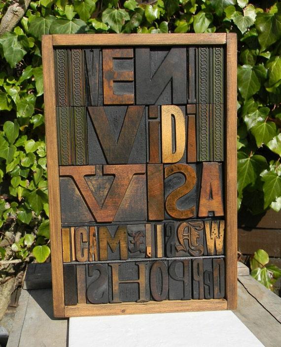 Collage of vintage wooden printing blocks Veni, Vidi, Visa presented in a letterpress case