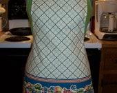 Full size retro apron, blue on blue, with fruit motif along the bottom.