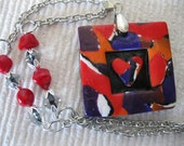 Chunky Polymer Clay 3-D Heart Pendant in red, black, orange and purple on silver chain with coral beads