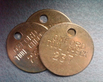 vintage brass stamped tags. tool room check tags. 1.25 inch diameter.