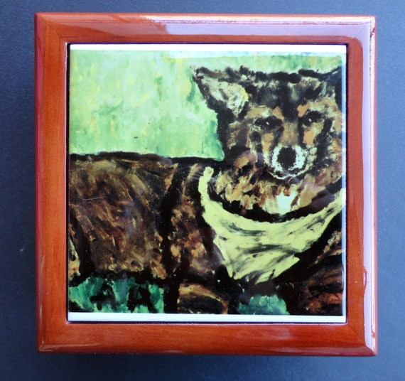 5.25x5.25 Polished mahogany wooden keepsake box with picture of  a sweet dog inlaid on the lid. Inside, is plush white velvet