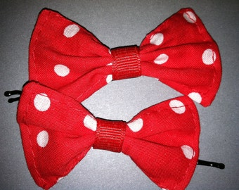 Pair of small red and white polka dot hairbows on bobby pins