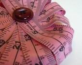 Pink tape measure flower brooch