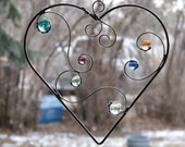 Love Flows - Suncatcher with flowing wire and multicolored glass gems inside a metal heart shaped ring.