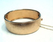 Gold textured vintage wide hinged cuff bracelet with safety clasp.