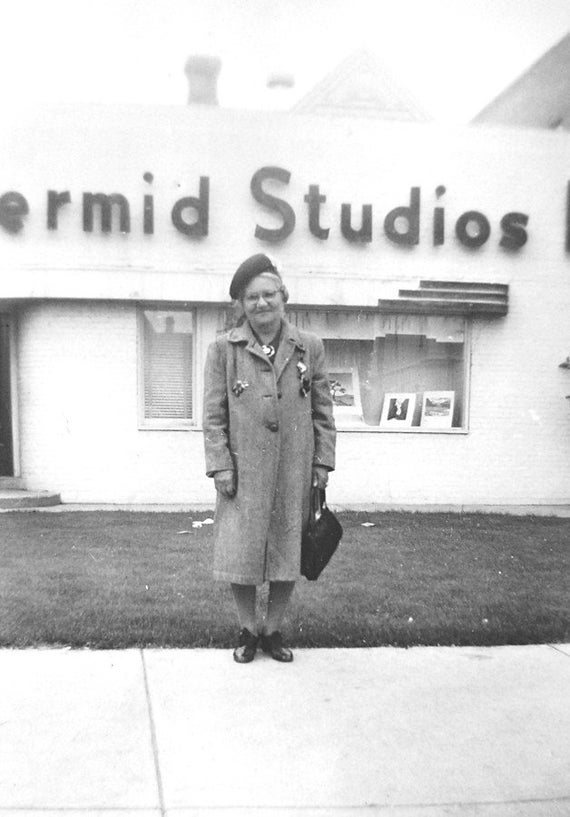 Vintage 1950s Photograph Woman Standing in Front of Photo Studio Smiling.