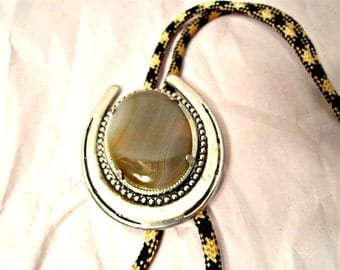 Slide Bolo Tie. Silvertone metal and gem stone cabochon. Cream and black woven cord.