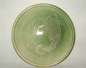 Shallow Bowl with rim featuring a Celadon Green Glaze with a slip trail large fish design on the interior of the bowl