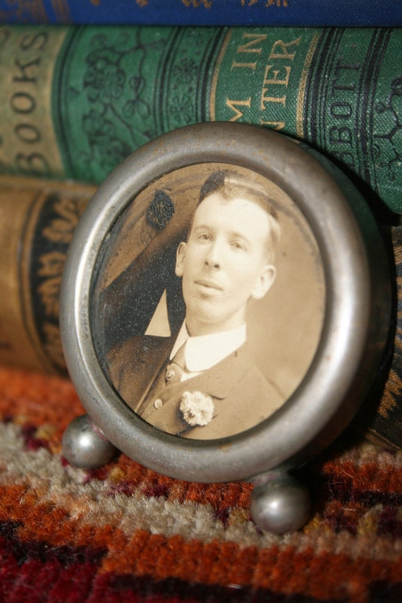 a platincid frame and photograph of a dapper young man from a bygone era