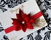 Gloria, a festive elastic headband featuring sparkly poinsettia leaves and rhinestones